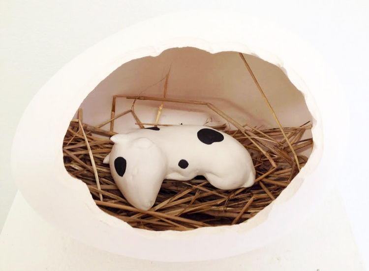 Sleeping baby cow in an egg